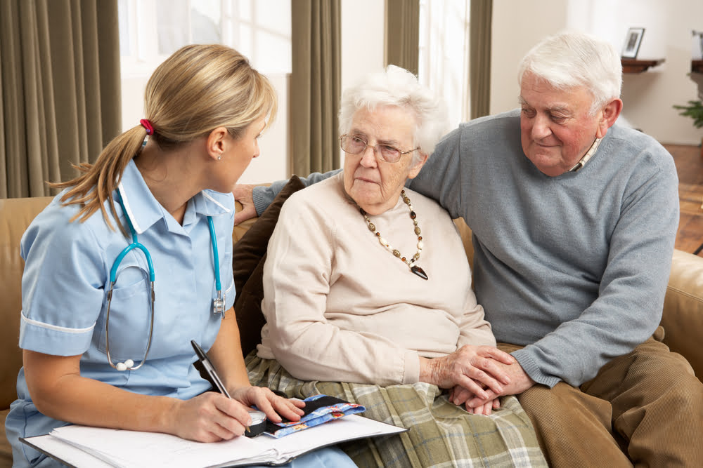 Two older people being visited by a nurse.